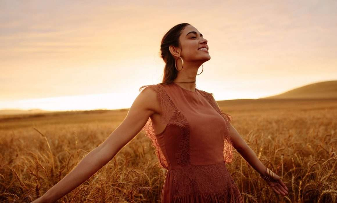 woman-standing-among-wheat-field-at-sunset-eco-friendly-brands-blog-post