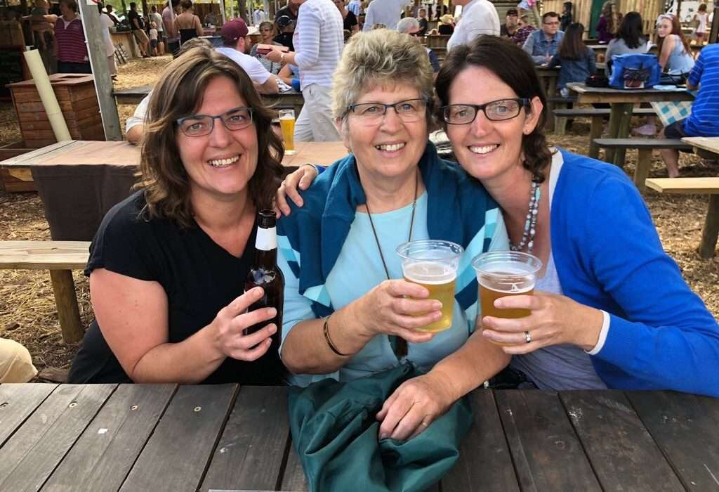 mother-and-two-daughters-picnic-table-toasting-a-drink-mothers-day