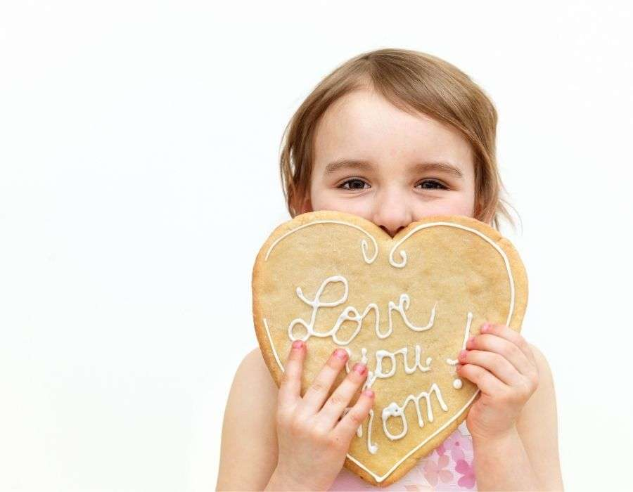 little-girl-giant-cookie-covering-half-her-face-heart-shaped-love-you-mom-icing-letters-mothers-day-blog-post