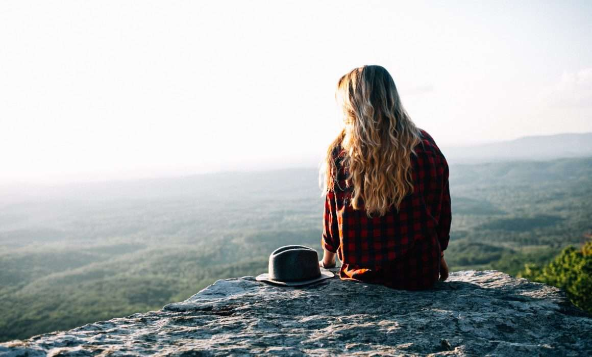 woman-sitting-on-rock-from-behind-long-blonde-hair-red-jumper-in-mindful-mood