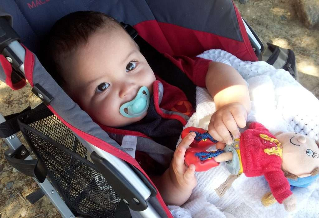 baby-in-stroller-dummy-in-mouth-big-brown-eyes
