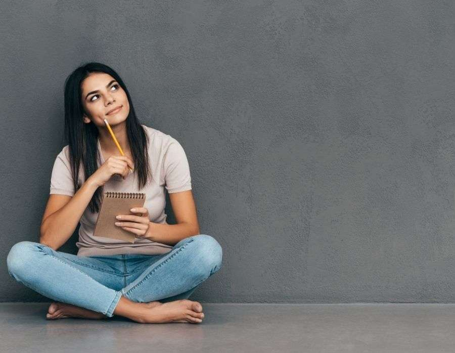 woman-sitting-crosslegged-against-grey-wall-tshirt-blue-jeans-long-dark-hair-holding-notepad-pencil-to-side-of-face-thoughtful-expression