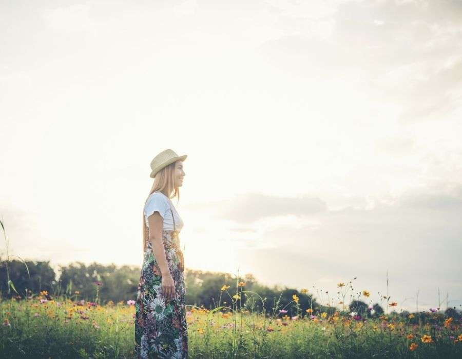 woman-long-blonde-hair-straw-hat-standing-in-field-of-flowers-good-day-blog-post