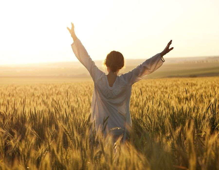 woman-in-field-sunset-wearing-white-arms-outstretched-to-the-sky-know-your-worth-blog-post