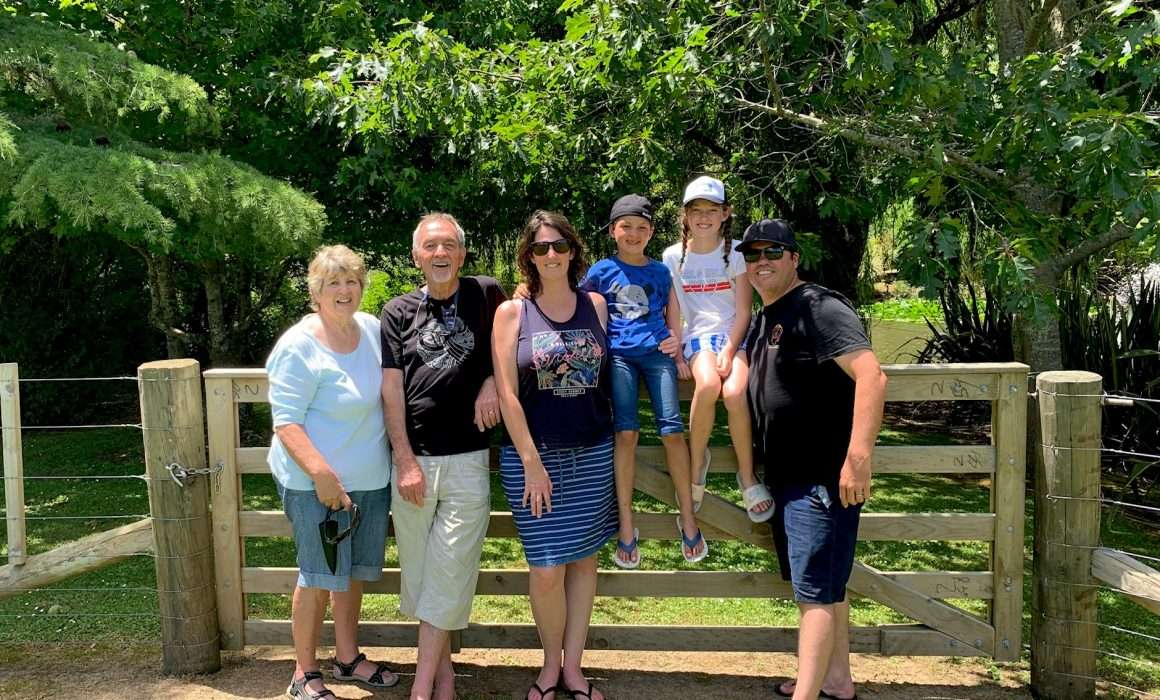 family-portrait-standing-in-front-of-large-farm-fence-trees-in-background-guidelines-from-parents-blog