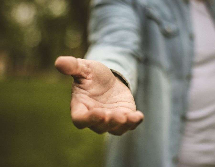 hand-reaching-out-to-help-blurred-forest-background