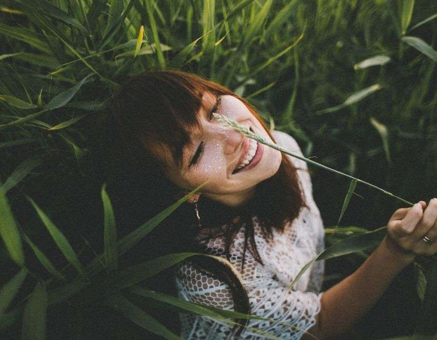 woman-in-tall-grass-smiling-face-to-sun-life-decisions-blog