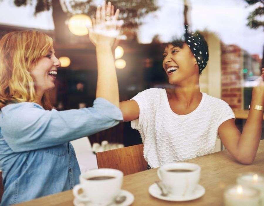 two-woman-high-fiving-smiling-giving-back-brings-joy