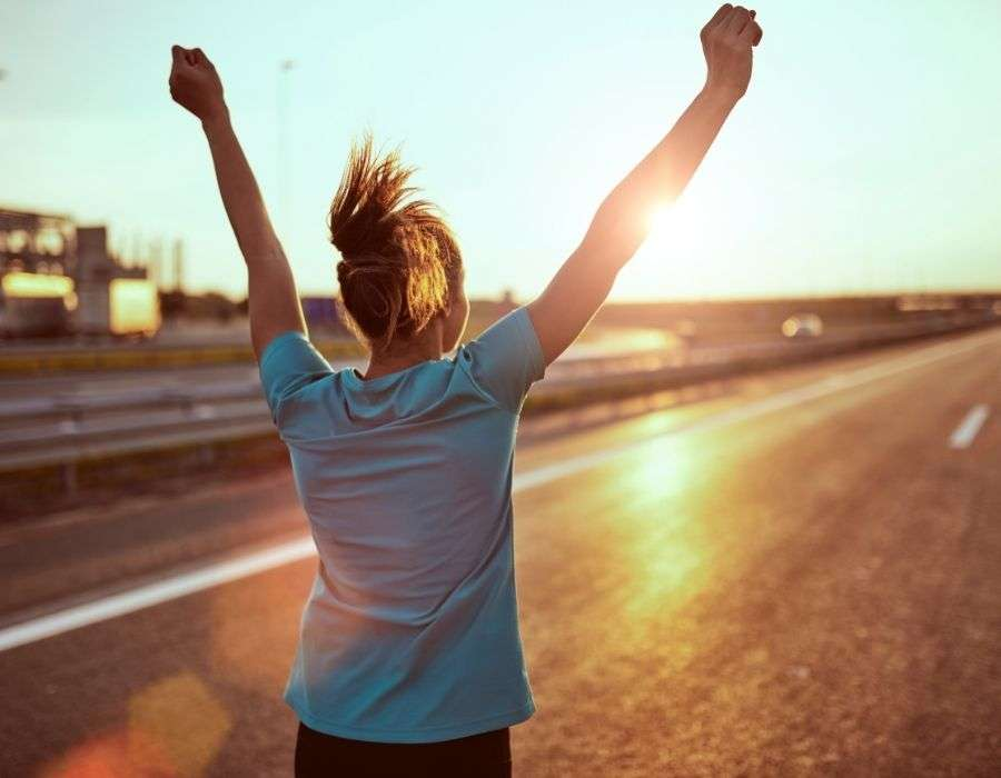 woman-ponytail-from-behind-open-road-arms-in-the-air-celebrating-being-strong